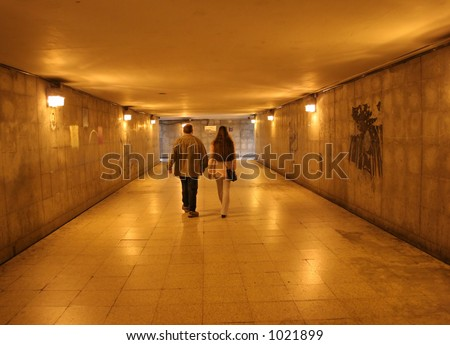 Two people walking through an underground tunnel