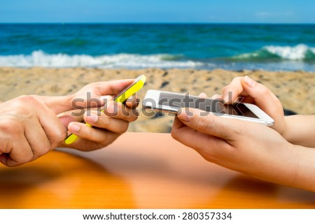 two people with the phone and connected to social networks in a beachside bar