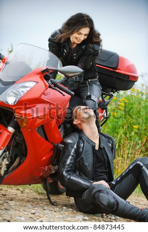 Two people: young beautiful woman sitting on motorbike and smiling man having rest.