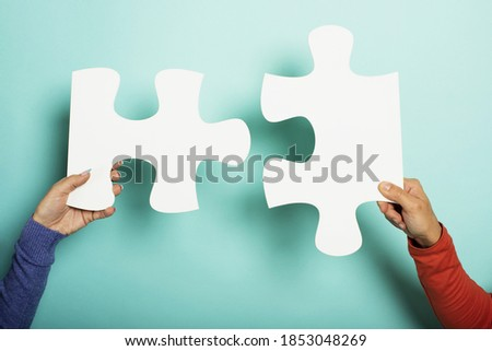 Two peoples join piace of puzzle. Concept teamwork, partnership, integration. Cyan background Stock fotó ©