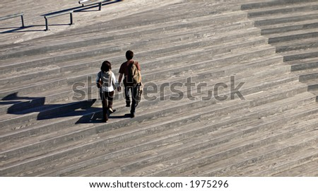 two peoples walking on the wooden stairs