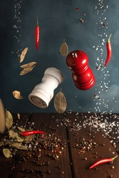 Two pepper shakers in flight, red and white. Levitation. Black Peppercorns and Spices