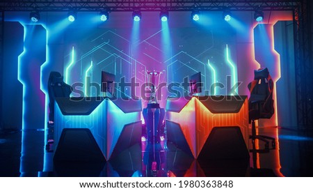 Two Person Empty Computer Gaming eSports Championship Arena with Winner Trophy Standing on a Stage. Stylish Online Live Streaming Tournament with Big Screens Showing Graphics and Neon Stage Photo stock ©