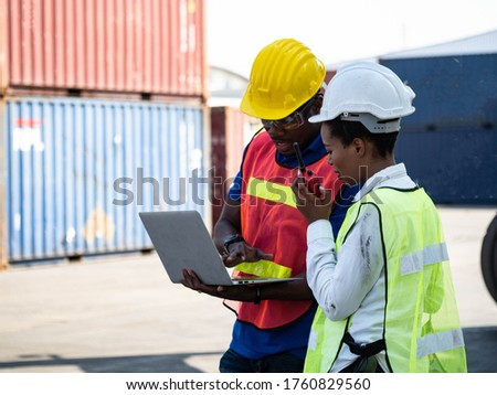 Two person foreman engineering helmet wear yellow and white safety green red are working computer pc notebook tablet and talk smartphone about import export investment technology digital at warehouse ストックフォト ©