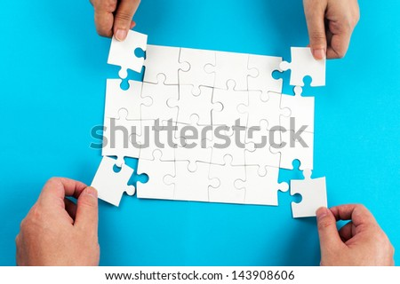 Two person holding jigsaw puzzle pieces and putting them together