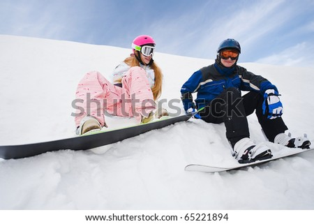 Two person sit on snow and preparing to ride from the hill