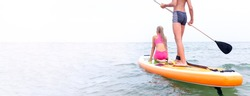 Two persons, boy and girl, on the paddle board on the calm sea surface moving forward to the horizon. SUP boarding, water sports. Active healthy lifestyle. Wide banner with copy space.