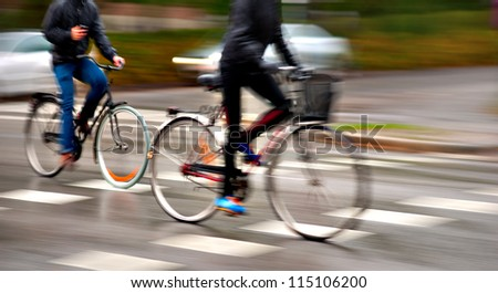 Two persons cycling on wet street on rainy day