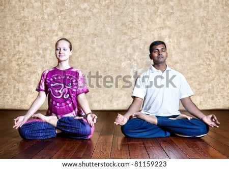 Two persons: Indian man and Caucasian woman in bright purple Indian cloth doing yoga meditation in padmasana lotus posture with dhyana mudra at the grunge background with wooden floor