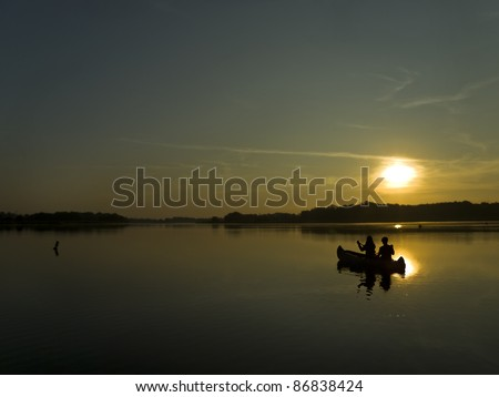 two persons sitting in a boat and facing dawn