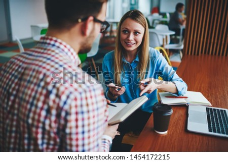 Two persons talking in coffee shop, experienced positive female graduate gives young male student basic tips choose strategy write course work successfully using modern devices applications web sites