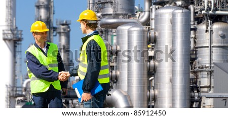 Two petrochemical contractors closing a deal in front of an oil refinary