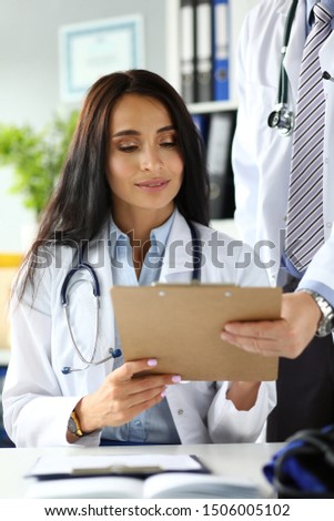 Two physicians discussing important documents clipped to pad portrait concept