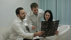 Two physicians in good mood analyze results of patient to diagnose disease, then comes intern with x-ray