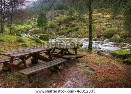 Two picnic tables in a park by the river in a cold rainy day - stock photo