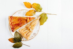 Two piece of apple and pear pie decorated with branches with leaves on wooden background. Autumn concept. Flat lay, top view