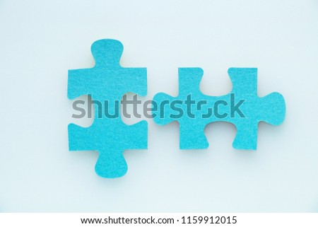 Two pieces of a puzzle piece on a white background.