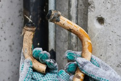 Two pieces of an old rusty bent plumbing pipe that has become unusable due to corrosion, a plumber in work gloves shows the time in the process of being replaced with modern communications