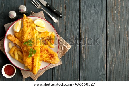 two pieces of battered fish on...