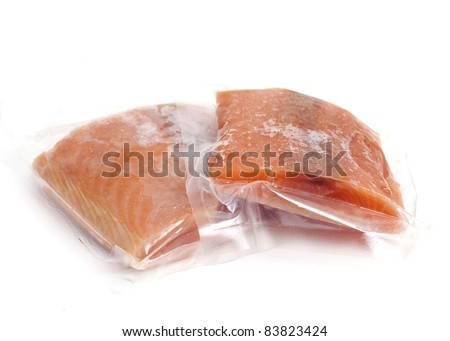 two pieces of frozen salmon on white background