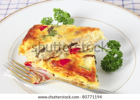 Two pieces of home-made Spanish omelet on a plate with a fork and garnished with parsley