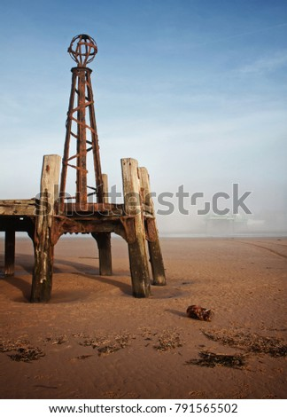 Two piers: with the newer pier obscured by mist and an abstract of the old pier bathed in winter sunshine at St Annes on the Sea #791565502