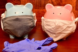 Two piggy banks, one pink and one blue wearing face masks and standing behind a rubber glove.