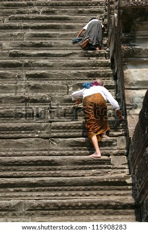 Two pilgrims climb to the highest tower at the Buddhist temple complex of Angkor Wat, in the Cambodia jungle