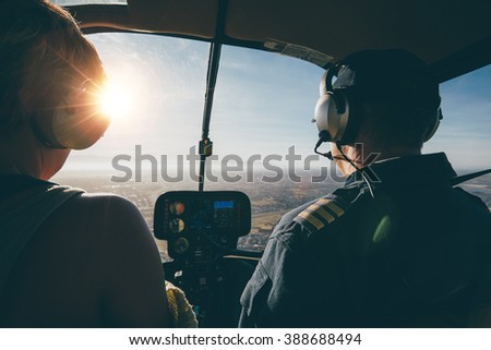 Two pilots in a helicopter while flying on a sunny day. rear view shot of man and woman pilots