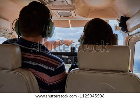 Two pilots sitting in a cockpit of cessna skyhawk 172 airplane.