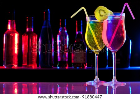 Two pink and yellow cocktails in the glass with straw and kiwi, and bar bottles row on the background