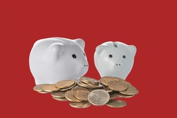 two pink ceramic piggy banks behind a bunch of copper coins on a colored background