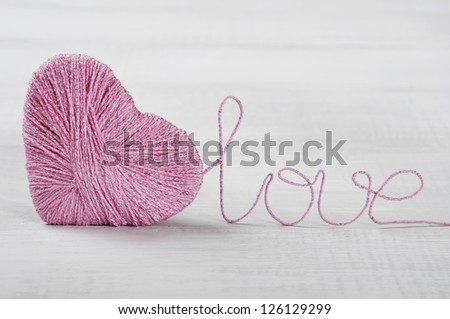 Two pink clews in shape of heart on white wooden background