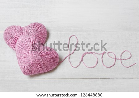 "Two pink clews in shape of heart with word  ""love"" made from yarn on  white wooden background"