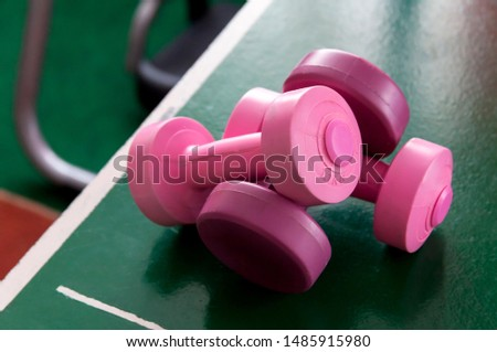 Two pink dumb bells laying on the table pong table. Feminine workout symbol, new female gym area heavy training and weight lifting equipment abstract, women's health concept, dumbbells on the table