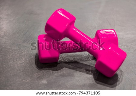 Two pink dumbbells lie crosswise on the gray floor on the right side of the photo. #794371105