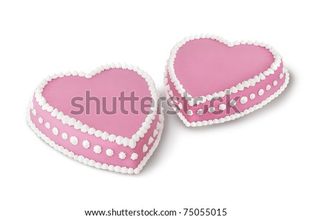 Two pink heart shape marzipan cakes decorated with white whipped cream