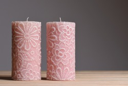 Two pink new candles with lace embossing on a gray background