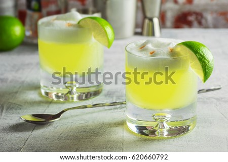 Two Pisco Sour Cocktails in Glasses with a Lime and Ingredients on the Bar #620660792