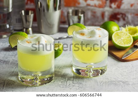 Two Pisco Sour Cocktails with Ingredients and Bottles on a Bar #606566744