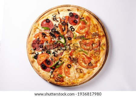 two pizzas in one. one half is a margarita, the other half is a salami. on a white background Foto stock ©