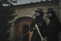 two plague doctors in masks on medieval castle background. Reconstruction of medicine costumes. Mascarade historical costumes and mask