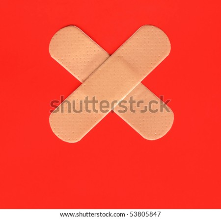 Two plasters forming a cross on red background