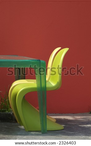 Two plastic and a table in green and yellow against a dark red background