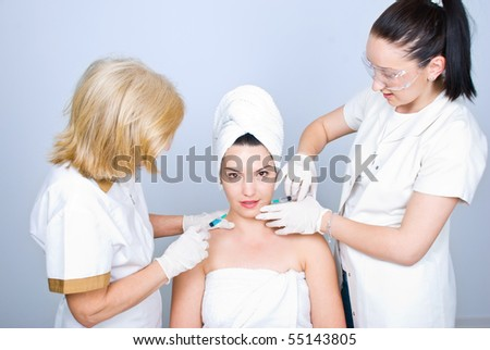 Two plastic surgeons giving an injection to a young  woman skin