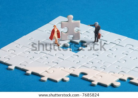 two plasticfigures standing on a puzzle with a hole in it