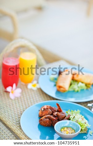 Two plates of delicious asian dishes and two glasses of fresh juices