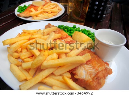 Two plates with fish, chips, peas and sauce on a table.