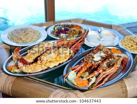 Two plates with lobster on table at window with view on ocean - stock photo