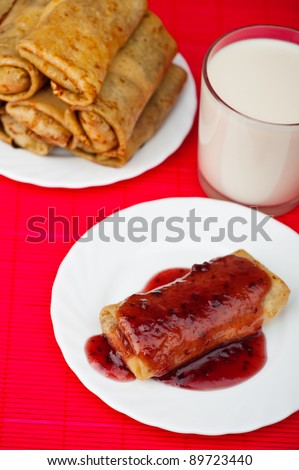 two plates with pancakes decorated with jam, glass of milk background pink tablecloth - stock photo